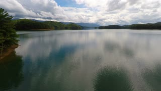 Aerial flight over an emerald lake cloudy day backward
