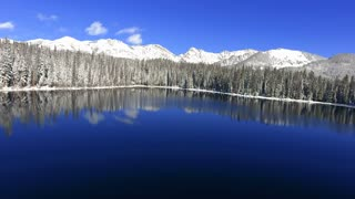 Aerial flight over reflective Rocky Mountain lake in winter with snow
