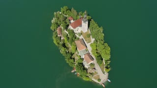 AERIAL: Flying above beautiful Bled lake island with small church