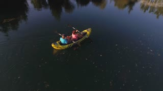 AERIAL: Flying above mature couple kayaking on river