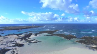 AERIAL: Flying across beautiful blue lagoons towards the lighthouse
