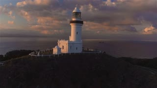AERIAL: Flying around lighthouse on small hill above beautiful ocean lagoon