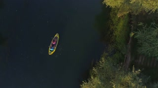 AERIAL: Flying around sporty couple kayaking along the river