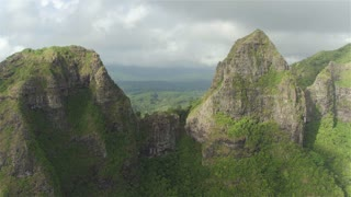 AERIAL: Flying between majestic mountain tops above lush rainforest jungle