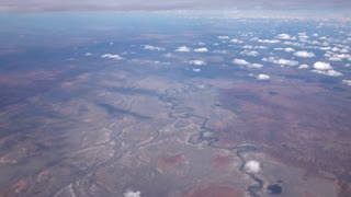 AERIAL: Flying high above bend watercourse of river in arid desert landscape