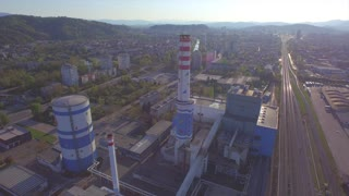 AERIAL: Flying over big chimney in heating plant in industrial city
