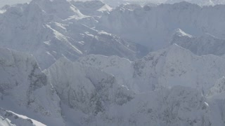 AERIAL: Flying over snowy mountains
