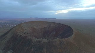AERIAL: Flying over the edge of a huge volcano crater