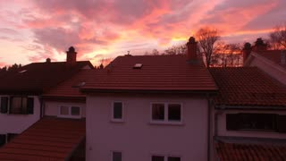 AERIAL: Flying over the suburban house towards the forest in reddish sunset