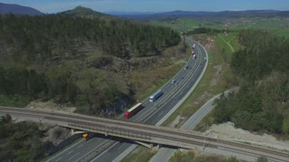 AERIAL: Freight trucks transporting the cargo on a freeway