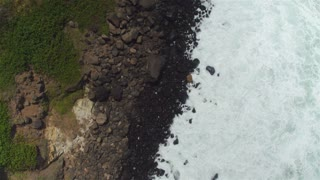 AERIAL: Grassy and stony black and green seashore from bird's perspective