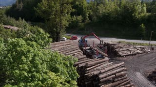 AERIAL: Loading stacked timber for transportation