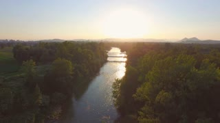 AERIAL: Magical golden sunset over wide fast current river with rocky bottom
