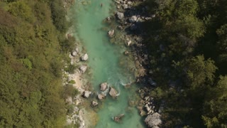 AERIAL: Man swimming down the crystal clear riverbed where people are kayaking