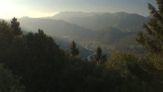 AERIAL: Meandering river winding through mountain valley in misty morning