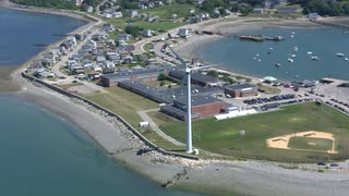 Aerial Push In On Beach Town Wind Turbine