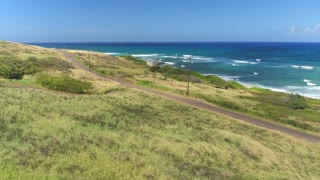 AERIAL: Red convertible driving along the coastal road in lush Hawaii island