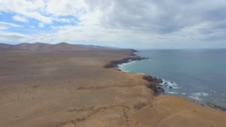 AERIAL: Rough volcanic coast with cliff above the ocean