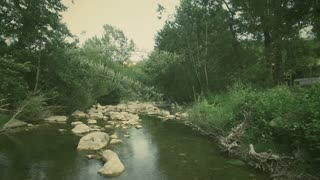 Aerial shot bridge over stream of water hidden on forest. 4k