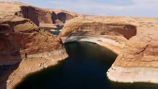 Aerial shot flying over peaceful water in Lake Powell through canyons