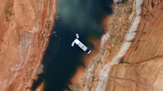 Aerial shot looking down at houseboat in Lake Powell