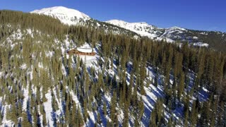 Aerial shot of a snow covered log cabin lodge in the woods with snowy Rocky Mountains in the background