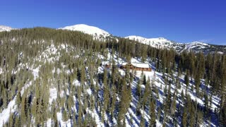 Aerial shot of a snow covered winter cabin in Colorado Rocky Mountains