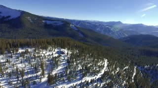 Aerial shot of a snowy cabin in the woods with Vail Ski Resort in the background