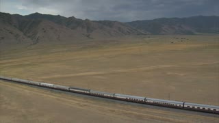 Aerial Shot Of Amtrak Train In Desert With Mountains