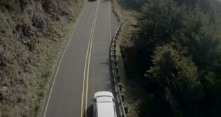 Aerial Shot of Cars traveling along a Mountain Side Road