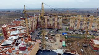 Aerial shot of construction site. Camera flies above new building under construction. Construction and Development concept