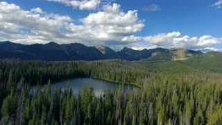 Aerial shot of Lost Lake in Colorado Rocky Mountains flying forwards with clouds and mountains