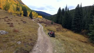 Aerial shot of offroading ATV rider on a dirt road in mountains with fall foliage autumn