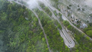 Aerial shot of the whole serpentine downhill road with moving cars