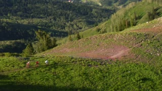 Aerial Shot Of Three Mountain Bikers On Green Mountain
