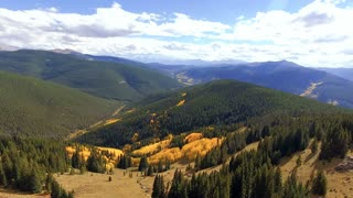 Aerial shot revealing vibrant fall foliage in autumn in Colorado Rocky Mountains
