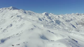 AERIAL: Ski slope in snowy mountains