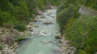 AERIAL SLOW MOTION: Turquoise rapid river running through woods