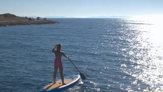 AERIAL: Smiling young woman standing on paddleboard with hands lifted in the air