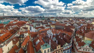 Aerial timelapse view of the traditional red roofs of the city of Prague, Czech Republic with the church of St. Jilji and the National Theatre in the background