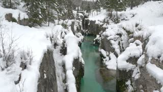 AERIAL: Turquoise river running through narrow canyon in winter