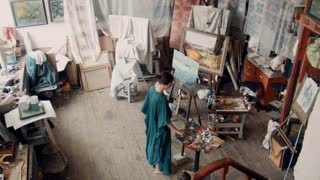 Aerial view of a female artist wearing a smock standing in her studio painting a canvas on an easel surrounded by other covered canvasses and art supplies