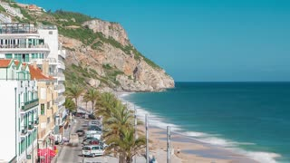 Aerial view on the coastal town of Sesimbra with palms on the street and beach in Portugal timelapse with blue sky and ocean 4K