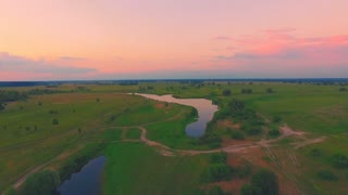 Aerial View: Slow Flight over the Beautiful River and Green Valley. Bright colors. Sunset soft light. Beauty world. Ukraine, Europe. 4K resolution