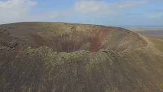AERIAL: Young woman hiking on the edge of volcano crater