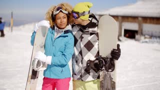 Affectionate young couple posing with snowboards