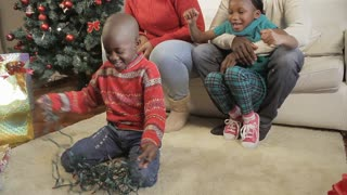 African American boy playing with christmas lights