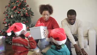 African American family opening their christmas gifts