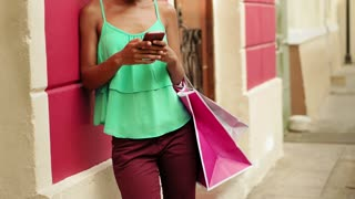 African American Girl Shopping And Text Messaging On Phone