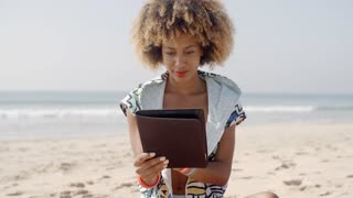 African American Girl Using Tablet Pc At Beach